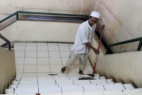 Marbot Masjid At-Tujar sedang membersihkan tangga masjid