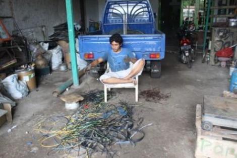 Seorang pekerja sedang mengupas kabel