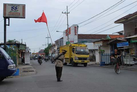 Pak Tris, seorang Polisi Cepek, bertugas dengan kostum Komandan