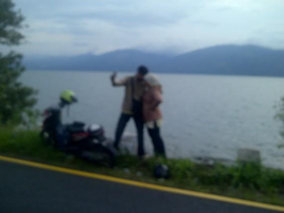 Wisatawan yang sedang berfoto di tepi Danau Singkarak (tahun 2013).