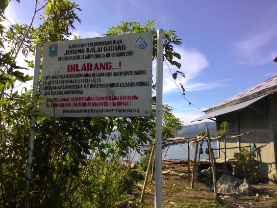 Plang larangan menangkap ikan dengan cara-cara ilegal, di dekatnya adalah tempat para nelayan menepikan perahunya,